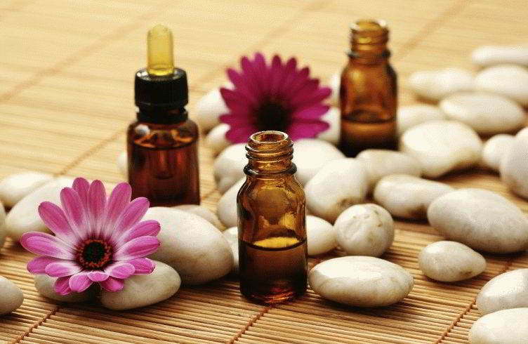 bottles of essence oil with pink flowers - beauty treatment