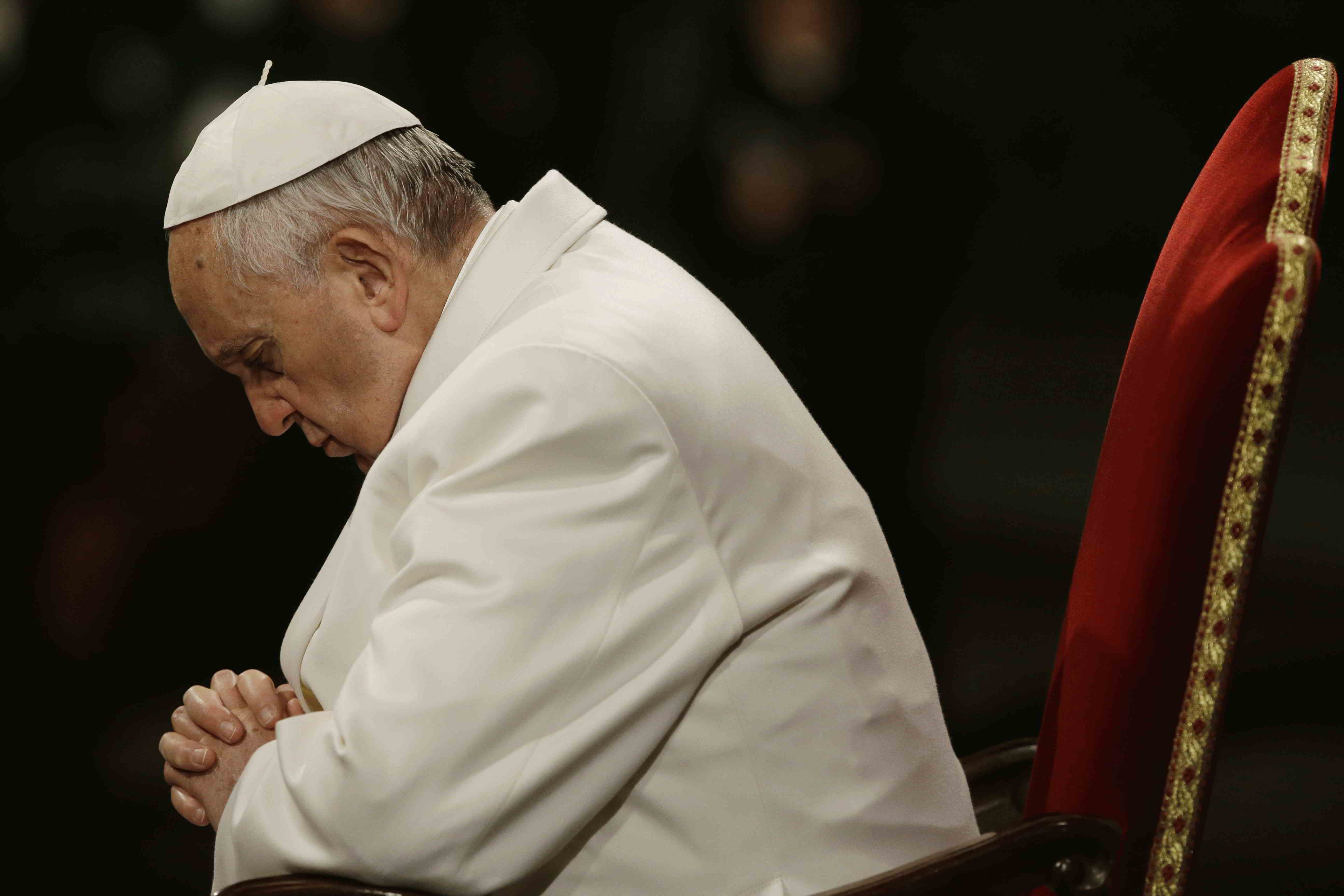 Pope Francis prays in front of the Colosseum during the Via Crucis (Way of the Cross) torchlight procession celebrated by Pope Francis on Good Friday in Rome, Friday, April 3, 2015. (AP Photo/Gregorio Borgia)