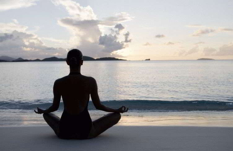 silhouette shot of woman practicing yoga at the Caribbean beach during sunset or sunrise
