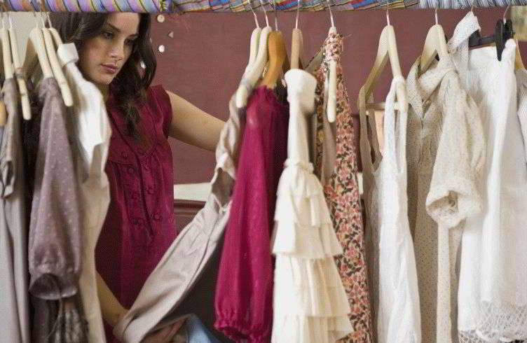 Woman browsing through rack of clothes