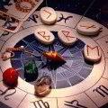 zodiac with runes, healing stones, magic pendulum and tarots in mystical lightining